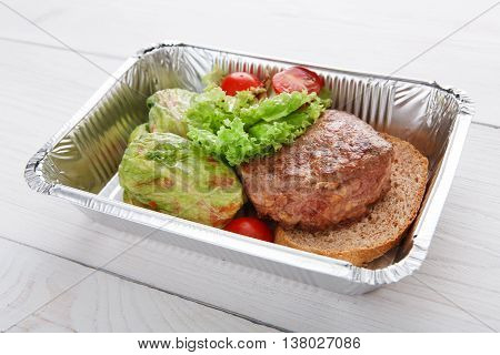 Healthy restaurant food delivery in foil box. Creative cuisine. Green stewed cabbage roll with veal steak on brown bread. Beef and vegetable with cherry tomato. Restaurant dish take away closeup.