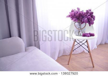 Lilac bouquet in glass jar on white stool