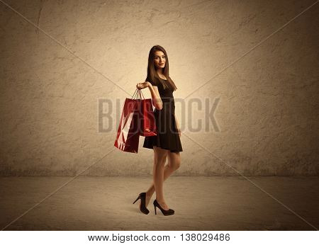 A beautiful young girl standing with red shopping bags in front of clear empty sepia urban wall background concept