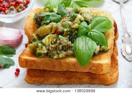 Baked Eggplant On Bread Croutons With Garlic, Cilantro And Basil. Spicy Snack. Selective Focus