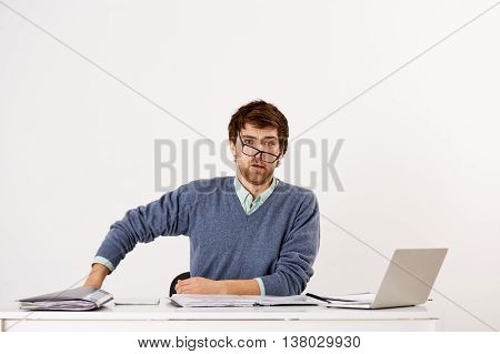 Handsome tired young businessman in glasses sitting at the office desk. Looking at camera. Isolated on white background.