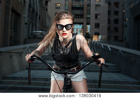 The woman in glasses on a bicycle in the city at night it is a biker.