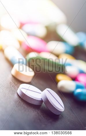 Pharmacy background on a black table. Tablets on a black background. Pills. Medicine and healthy. Close up of capsules. Differend kind of pills. Sunlight on the left corner of picture