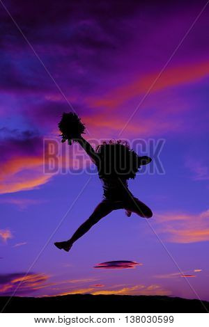 A silhouette of a woman jumping in the air with her pom pom.