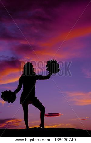 A silhouette of a woman cheerleader with her pom poms in the outdoors.