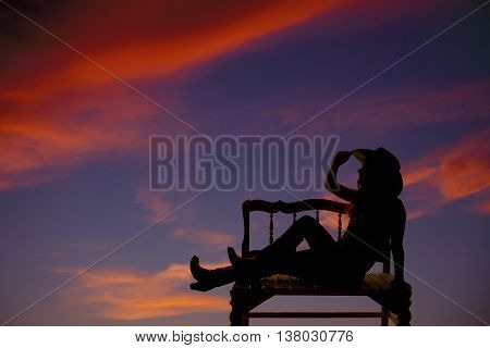 A silhouette of a cowgirl sitting on a bench relaxing with a beautiful sunset.