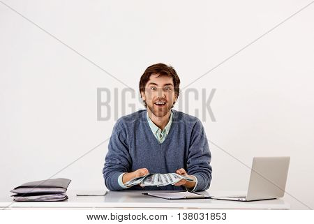 Handsome smiling young businessman sitting at the office desk with money in his hands. Looking at camera. Isolated on white background.
