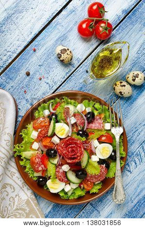 Salad with fresh vegetables feta cheese quail eggs olives and salami. Plate with salad on a blue wooden background. Top view