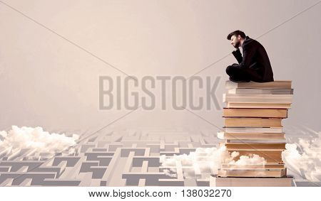 A serious businessman in suit sitting on a pile of giant books in front of a grey wall with clouds, labirynth