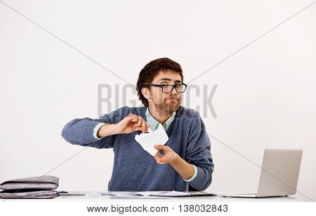 Handsome funny young businessman in glasses sitting at the office desk working with papers. Looking at camera. Isolated on white background.