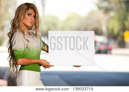 Transgender person holding blank sign street side for advocation phrases.
