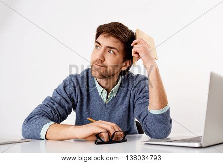 Handsome thinking young businessman sitting at the office desk. Looking away. Isolated on white background.