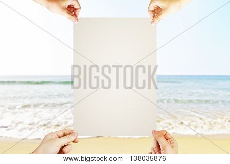 Four hands holding blank poster on seaside background. Mock up