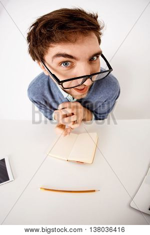 Funny and crazy interested handsome young businessman in glasses sitting at the office desk on white background. Looking at camera. Wide angle.