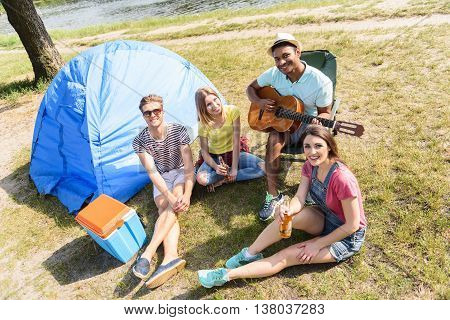 Happy friends are resting near river. They are sitting on grass near tent and smiling. Women are drinking beer. Man is playing guitar
