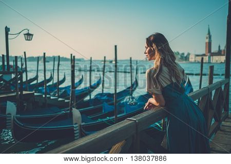Beautiful well-dressed woman standing near San Marco square with gondolas and Saint George island on the background.