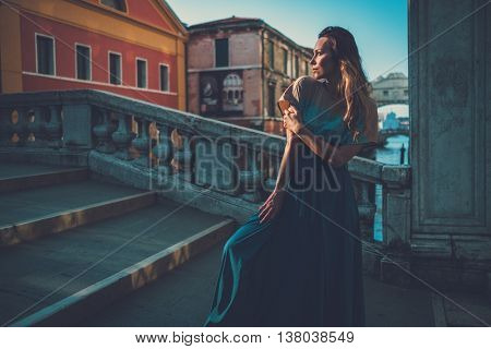 Beautiful well-dressed woman posing on a bridge over the canal in Venice.