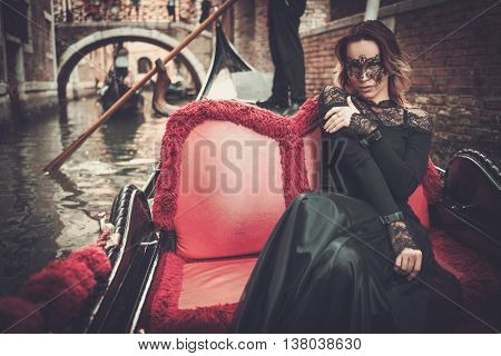 Beautiful woman in black dress with carnaval mask riding on gondola.