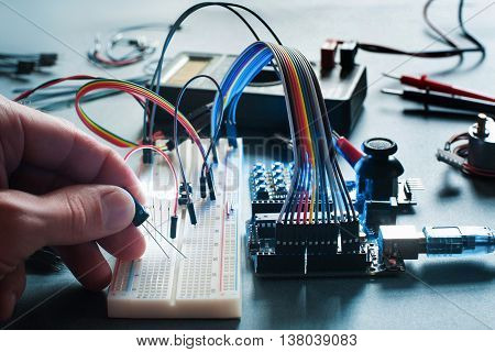 Circuits creation with electronic components. Closeup on programmer hand connecting led with breadboard and microcontroller. Programming, electronics development, innovation in technologies