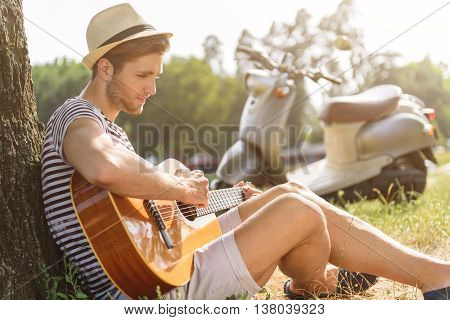 Pensive young man is playing guitar with inspiration. He is sitting on grass and leaning back on tree. Scooter on background