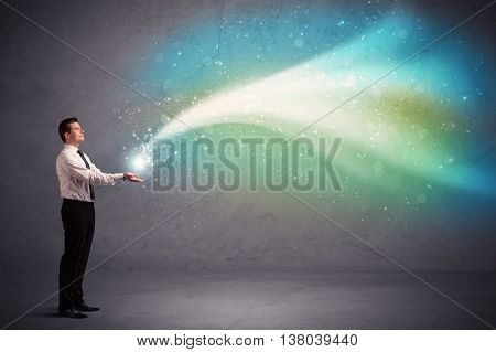 Caucasian businessman holding aurora borealis kind of ray of light