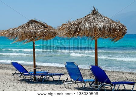 Blue Deck Chairs Overlooking The Tropical, Turquoise Ocean Under A Straw Umbrella On White Sandy Bea