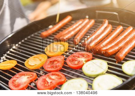 Close up of appetite vegetables and sausages on grill