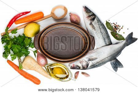 Top view of open empty casserole fresh fish raw vegetable and spices for soup isolated on white background.
