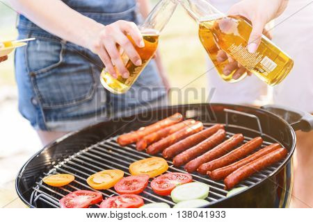 Cheers. Friends clinking bottles of beer under grill. Close up of barbecue and human hands
