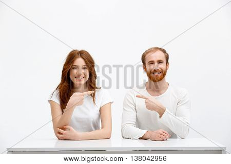 Funny redhead boy and girl sitting at white desk over white background and point finger to each other.
