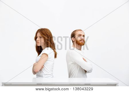 Offend redhead girl and boy sitting at white desk over white background