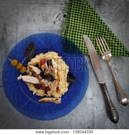 Traditional italian risotto with chicken tomato basil and parmesan on blue plate with knife and fork on napkin against rustic wooden background top view