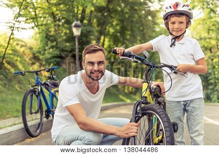 Handsome young dad and his cute little son are riding bikes in park looking at camera and smiling. Father is examining his son's bicycle