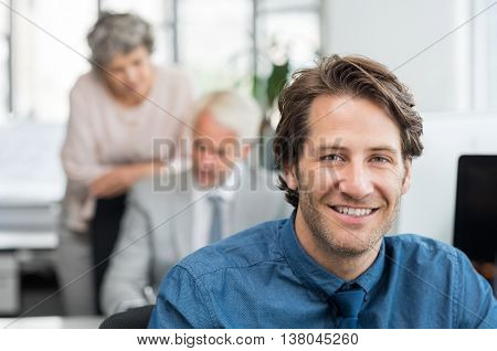 Close up face of handsome young businessman smiling in office. Portrait of a young broker sitting at office and looking at camera while financial experts working at computer at background.