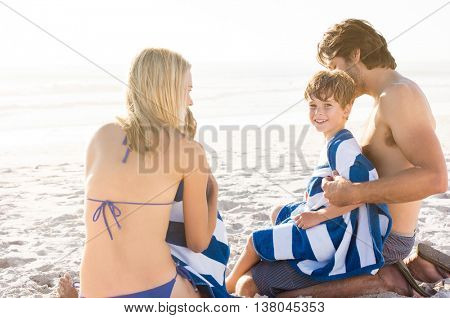 Young boy sitting on father lap with towel after swin at sea. Father draping towel on son after swimming. Smiling son looking at camera at beach with his family.