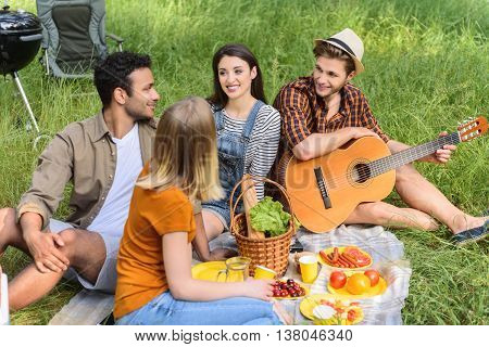 Happy men and women relaxing on picnic in forest. They are talking and smiling. Friends are sitting on blanket on grass