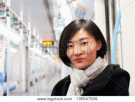 An attractive chinese woman sitting on an empty metro car wearing a winter coat and scarf in Shanghai China.