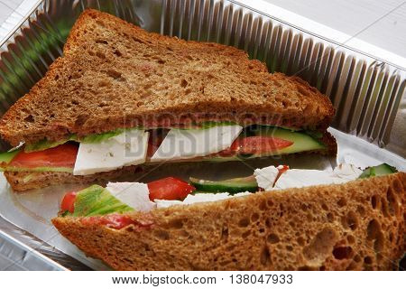 Healthy lunch and diet concept. Take away of fitness food. Weight loss nutrition in foil boxes. Sandwiches with whole-grain bread, cucumber, feta cheese and tomatoes at white wood, closeup