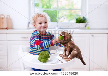 Happy little boy in high chair eating broccoli and feeding his toy dinosaur in a white kitchen. Healthy nutrition for kids and baby. Bio vegetable as solid food for infant. Children eat vegetables.