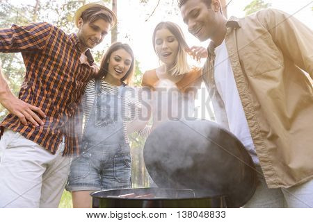 What appetite barbecue. Hungry young friends are looking at food on grill with amazement. They are standing in forest and smiling