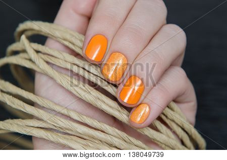 Beautiful female hand with warm orange nail design.