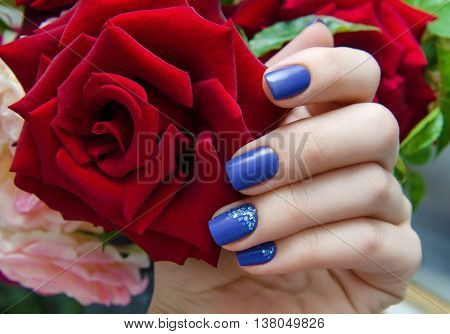Beautiful female hand with purple nail design and red rose.
