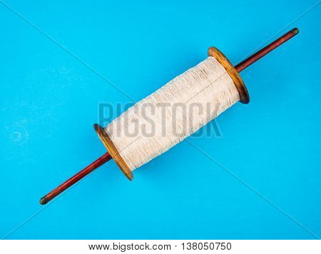 A beautiful spindles with white thread to fly kites, isolated on blue background, selective focus