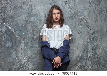 Bright fashion portrait of pretty young brunette teen hipster woman with bright make up and stunning curled brunette hair wearing sportive outfit on urban background