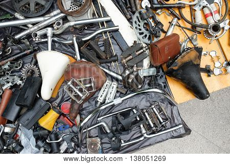 Old bicycle spare parts and accessories in heap offered for sale