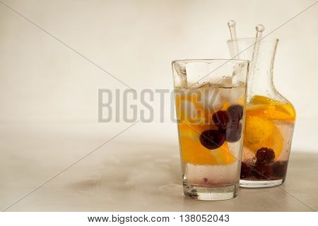 Fizzy lemonade with oranges and cherries in transparent glass jug with glass on the white background with copy space