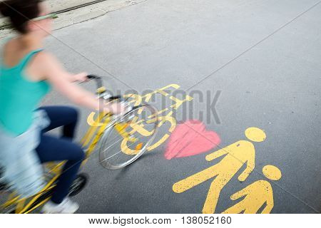 Woman in bike passing by the pedestrian/bicylce sign with heart painted on the sidewalk in Budapest
