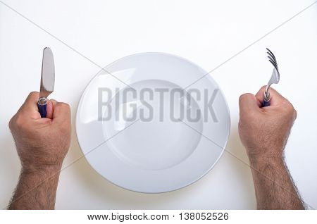 hands of a person holding a knife and fork and claim something to put in the empty plate that has in front of him