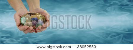 Crystal healer's website banner - female hands holding and offering a selection of healing crystals in a round brass dish on a flowing graduated blue jade colored wide background with copy space