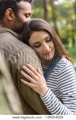 I like be with you. Young loving couple is embracing with love. They are standing in park. Woman closed eyes with enjoyment and smiling